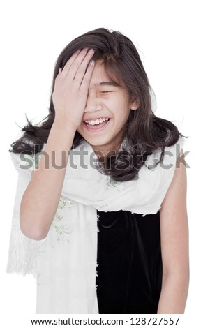 Young biracial asian girl slapping herself on the head, laughing