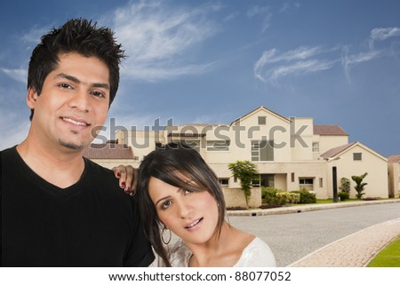 young biracial couple in front of their new home
