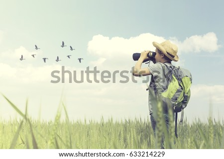 Young birdwatcher looks with his binoculars the bird world