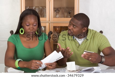 Young black African American couple sitting by glass table and trying to work through pile of bills, frustrated by amount of expenses during economic crises recession times