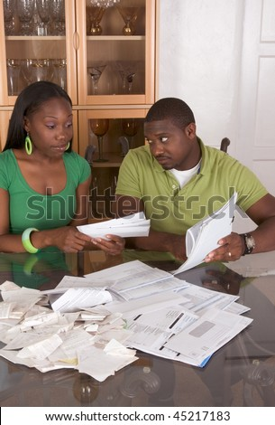 Young black African American couple sitting by glass table and working through pile of bills, frustrated by amount of expenses during economic crises recession times hoping for stimulus plan to work