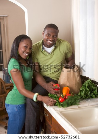 stock photo : Young black African American couple sorting vegetable on kitchen countertop