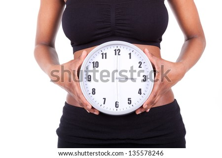 Young black african american woman holding a clock in front of her belly, isolated on white background - African people