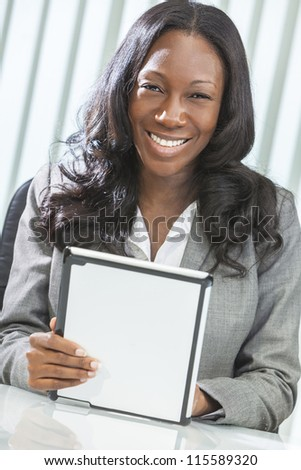 Young black African American woman or businesswoman in smart business suit using a tablet computer