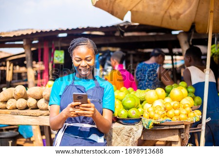 young black African businesswoman in a local market browsing online using smartphone checking  reading news online