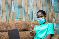 young black African freelancer working from home wearing nose masks preventing the spread of Corona virus