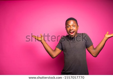 young black african man standing on a pink wall  raising his arms wondering about some sitting things with facial expression .reaction concept