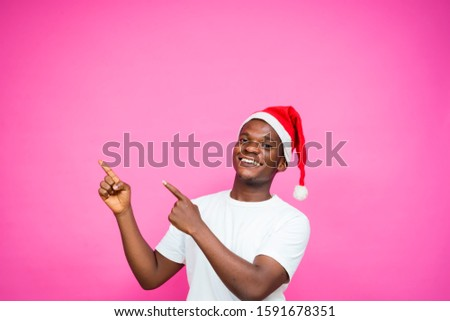 young black African man wearing Christmas hat standing on a pink wall showing a free space for advert purpose
