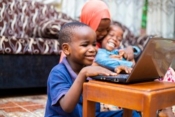 young black african preschool kid using technology having online class at home