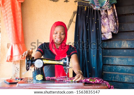 young black African woman sawing  using analog  sawing machine sitting in her small local shop