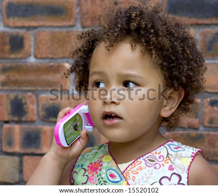 Young black baby girl talking on a toy cell phone