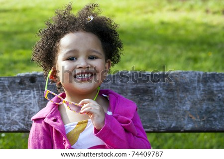 Young black baby girl with glasses smiling