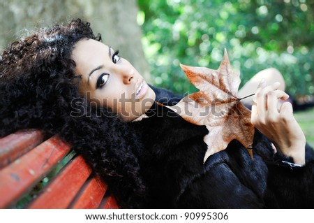 Young black beautiful woman siting on bench in park