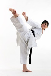 Young black belt karate fighter training hight kick . Isolated woman portrait on white background
