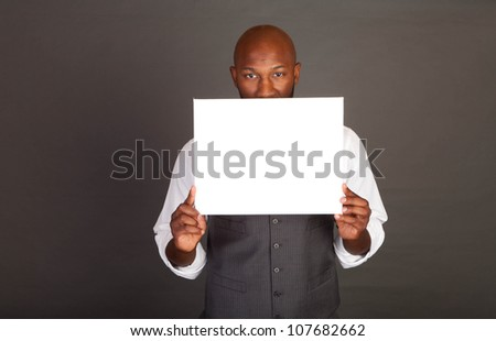 Young black business man holding a white card in front of his face
