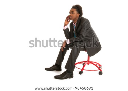 Young black business man with mobile phone sitting in studio