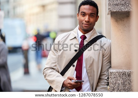 Young black businessman leaning on a wall in the street in London holding phone and smiling to camera, selective focus