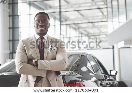 Young black businessman on auto salon background. Car sale and rent concept.