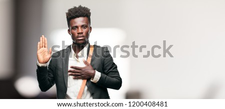 young black businessman smiling confidently while making a sincere promise or oath, solemnly swearing with one hand over heart.