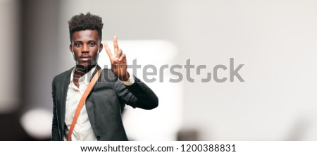 young black businessman with a proud, happy and confident expression; smiling and showing off success while gesturing victory, giving an