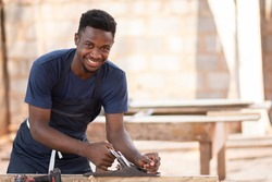 young black carpenter smiling while working
