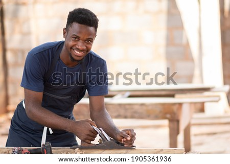 young black carpenter smiling while working Stock photo ©