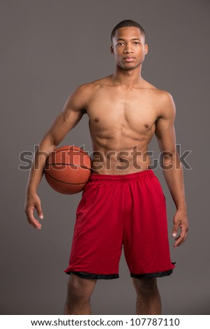 Young Black College Student Holding Basket Ball on Grey Background
