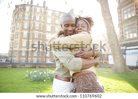Young black couple hugging in a park at sunset while visiting London city.