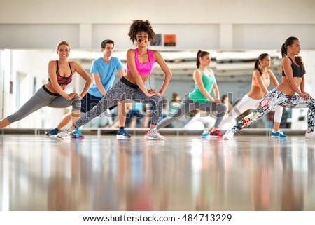 Young black curly trainer with group training aerobic at gym