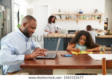Young black family busy working in their kitchen