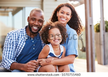Young black family embracing outdoors and smiling at camera