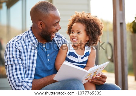 Young black father and daughter reading book outside #1077765305