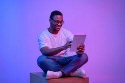 Young black freelancer guy in glasses sitting with digital tablet under luminous neon light, african american man blogger working online, browsing internet and enjoying modern techologies, copy space