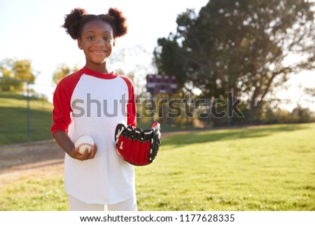 Young Black girl holding baseball and mitt looking to camera