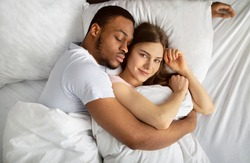 Young black guy sleeping and hugging his beautiful Caucasian girlfriend in bed, top view. Overhead shot of affectionate multiracial couple cuddling together in morning