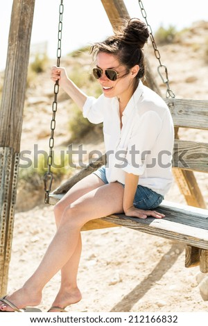 Young black hair woman sitting on the swing in the desert background. Low depth of field. Attractive girl looking out over a dramatic valley in the Negev desert in Israel.