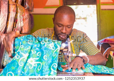young black male tailor working with his sewing machine