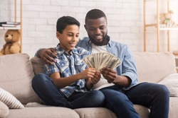 Young Black Man Counting Dollar Cash Money With Son, Explaining Him Financial Accuracy, And How To Earm money, Sitting On Sofa At Home Together