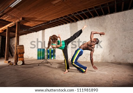 Young Black man dodging a Capoeria kick with berimbau player in back