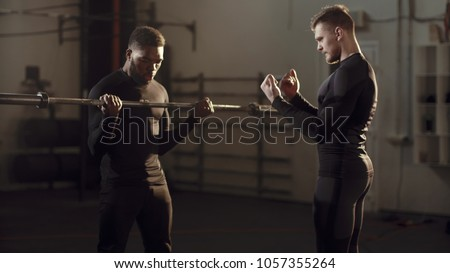 Young black man doing exercises with a personal trainer as he lifts a barbell weight to chest height in a gym in evening