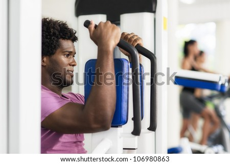 Young black man exercising pectoral muscles in fitness club, with people working out on cyclette in background
