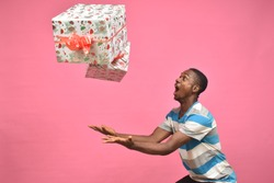 young black man feeling excited while catching gift boxes