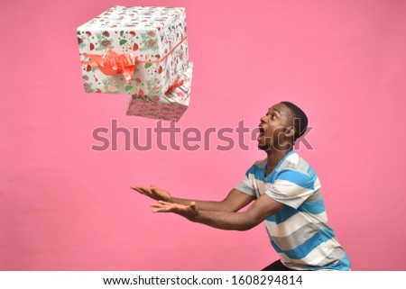 young black man feeling excited while catching gift boxes Stock foto ©