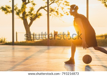 young black man playing basketball on court, morning exercises, active lifestyle, warm sunlight, doing sports on sunrise