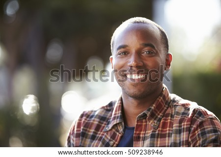 Young black man sitting outside, head and shoulders portrait