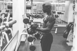 Young black man training with dumbbells inside gym during night time - African guy doing fitenss workout session - Sport and body building concept - Focus on face - Black and white editing
