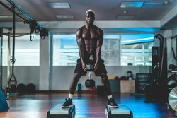 Young black man training with dumbbells inside gym during night time - African guy doing fitenss workout session - Sport and body building concept - Soft focus on face