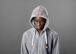 Young Black man wearing a grey hoodie looking down with a serious sombre expression in a close up head and shoulders portrait on grey