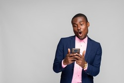 young black man wearing a suit looking at his phone, looking thrilled and surprised