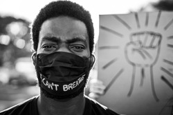 Young black man wearing face mask during equal rights protest - Concept of demonstrators on road for Black Lives Matter and I Can't Breathe campaign - Focus on eyes - Black and white editing